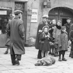 zdjęcie wykonane podczas wojny w getcie żydowskim. na zdjęciu ludzie stojący na chodniku i z zaciekawieniem patrzący w stronę obiektywu. jedna osoba leży na ziemi, najprawdopodobniej nie żyje, ale nikt nie zwraca na nią uwagi.