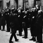 Zdjecie wykonano podczas wojny. na dziedzińcu budynku w rzędzie, z uniesionymi rękami stoją mężczyźni pochodzenia żydowskiego. przed nimi żołnierz niemiecki, prawdopodobnie trzyma broń, której na zdjeciu nie widać