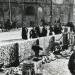 zdjecie pochodzące z czasów wojny. mężczyźni budują mur. jest to mur getta warszawskiego. w tle ciągnięte przez konie karoce