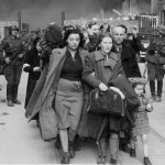 zdjęcie z czasów wojny, getto warszawskie, grupka kobiet i męzczyzn prowadzona przez oddział żołnierzy niemieckich. w tle płomienie i dym