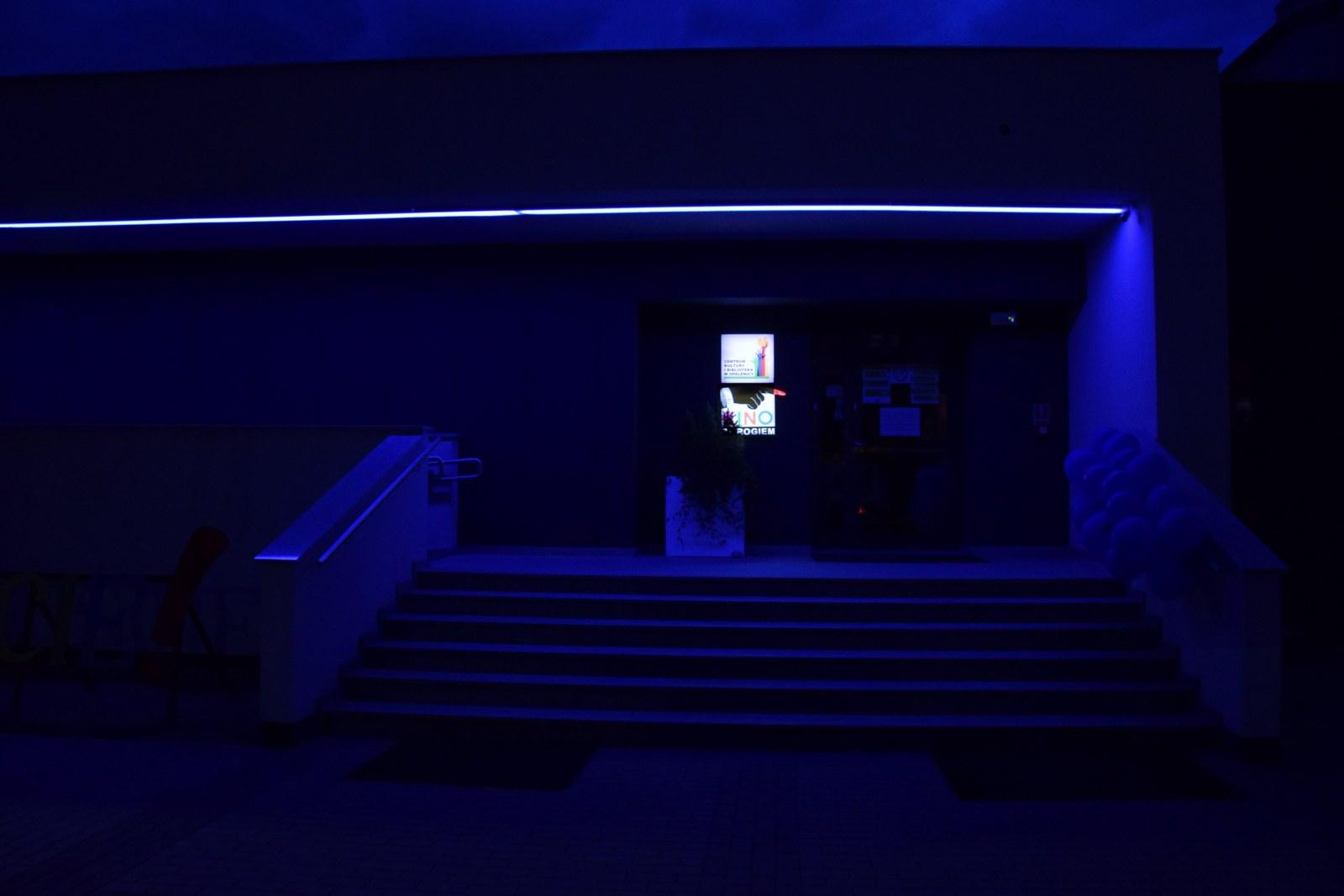 Zdjecie wykonane po zmroku. Wejscie do opalenickiego ckib rozświetlone niebieskim światłem. do poręczy schodów przywiązane niebieskie balony