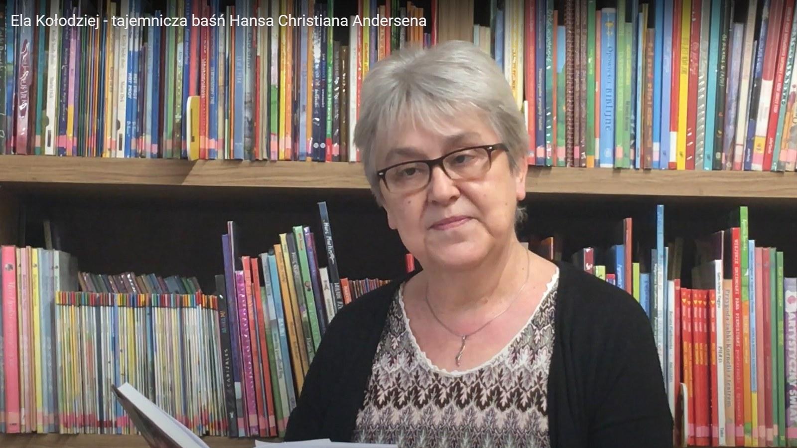 na zdjęciu uśmiechnięta, siwowłosa bibliotekarka w okularach siedząca na tle regału z książkami