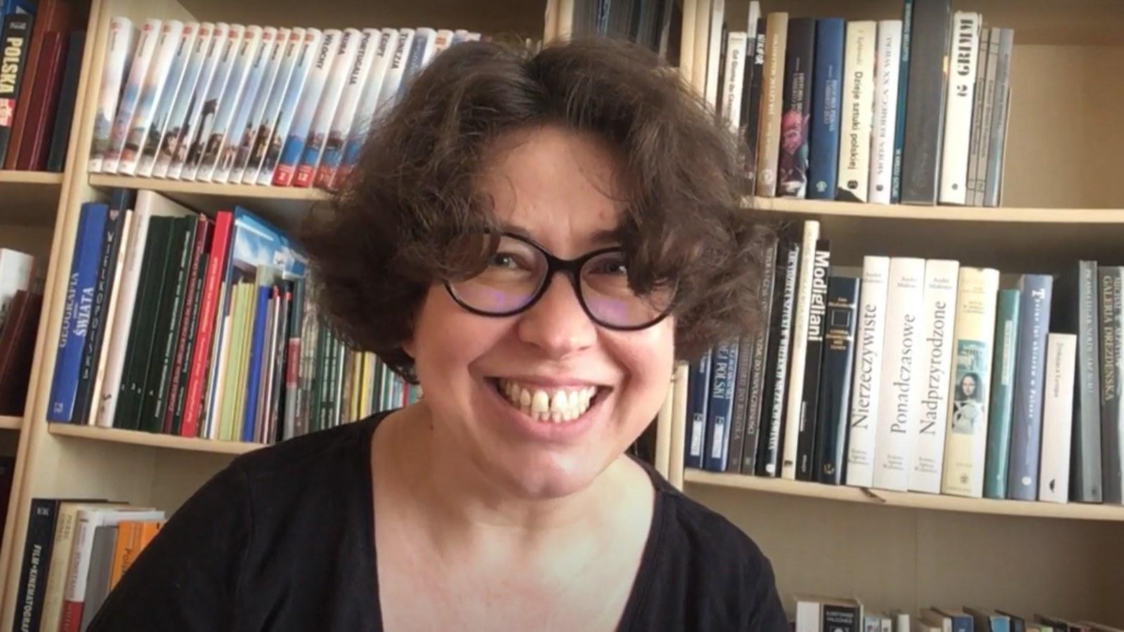 na zdjęciu uśmiechnięta bibliotekarka w okularach siedząca na tle regału z książkami