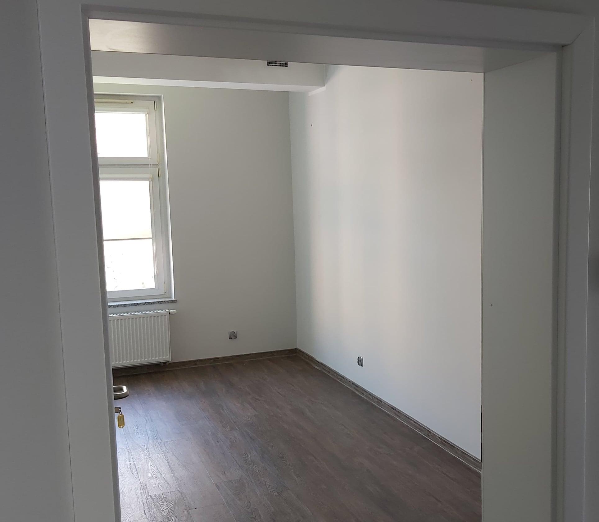 Na zdjęciu puste pomieszczenie. zdjecie zrobione przez drzwi z korytarza. przez okno pada słońce. w pomieszczeniu pomalowane na biało ściany o brązowa podłoga.