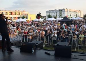 Zdjęcie zostało zrobione podczas koncertu, na pierwszym planie z lewej strony widzimy piosenkarza, w tle licznie zgromadzoną publiczność i budynki przedszkola i bloku w Opalenicy