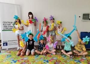 Zdjęcie zostało wykonane w pracowni Centrum Kultury i Biblioteka w Opalenicy, na dole zdjęcia znajduje się dywan, który ma wzór w kolorowe literki alfabetu, na dywanie siedzi szóstka dzieci, za nimi stoją cztery młode osoby i jedna dorosła z maseczce, wszyscy w rękach trzymają kolorowe balony, dzieci mają również balony na głowach, po lewej widać baner z hasłem Centrum Kultury i Biblioteka w Opalenicy