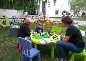 Na zdjęciu na pierwszym planie siedzą 3 osoby, dwie dorosłe i jedna młoda, siedzą na kolorowych krzesłach - niebieskie, zielone, w tle stoją ogrodowe krzesła w kolorze jasnym, a także biały budynek Centrum Kultury i Biblioteka w Opalenicy oraz fragment kolorowego napisu ze słowem - oczywiście