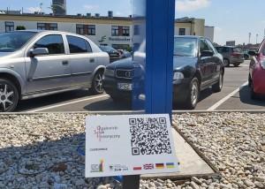 na zdjęciu na pierwszym planie tabliczka z kodem QR Opalenickiego Szlaku Historycznego, w tle samochody i budynek Cukrowni w Opalenicy, a także powierzchnia z jasnych kamieni