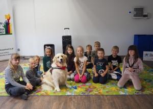 Zdjęcie zostało wykonane podczas zajęć z psem terapeutą. Jest to zdjęcie grupowe, na którym znajduje się 11 dzieci i pies rasy Golden Retriever. Dzieci i pies siedzą na kolorowym dywanie.