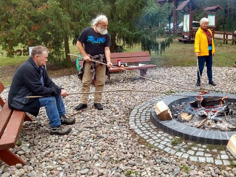 Zdjęcie zostało zrobione na dworze. Na zdjęciu jest trzech seniorów. Kobieta i mężczyzna stoją, jeden mężczyzna siedzi. Wszyscy trzymają kije z kiełbasami nad ogniskiem.