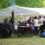 Zdjęcie przedstawia strefę jedzeniową. Po lewej stronie zdjęcia znajduje się kocioł na kołach z kominem, przy którym stoi mężczyzna. A po prawej kupujący. Za nimi siedzą osoby, które jedzą i rozmawiają.