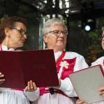 Na scenie znajdują się trzy starsze kobiety. Pierwsza o lewej i pierwsza po prawej trzymają teczki z zapisanymi słowami do śpiewu. Ubrane są w ludowe stroje.