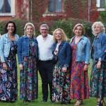 Zdjęcie przedstawia Opalenicką Grupę Wokalną. Jest to zdjęcie grupowe. 7 kobiet ma ubrane kolorowe suknie i jeansowe kurtki. Mężczyzna - dyrygent ma ubraną białą koszulę i czarne spodnie.