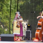 Na zdjęciu znajduje się zespół kotkowiacy. Ubrani są na ludowo. Trzymają instrumenty, akordeon, skrzypce i kontrabas.