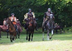 Na zdjęciu znajduje się gruipa rycerzy na koniach.