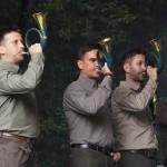 Na zdjęciu znajduje się zespół grający na rogach myśliwskich. Czterech mężczyzn ubranych w kolory leśne, trzymają rogi myśliwskie.