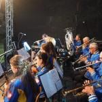 Zdjęcie przedstawia Opalenicką Orkiestrę Dętą w trakcie grania, po lewej stronie zdjęcia znajduje się dyrygent. Resztę kadru wypełniają muzycy uchwyceni w trakcie grania.