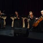 Zdjęcie zostało zrobione w sali widowiskowej CKiB, na scenie siedzi kwartet kobiecy smyczkowy