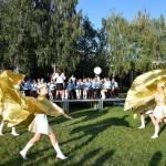 Zdjęcie zostało zrobione podczas Opalenickiego Przeglądu Orkiestr Dętych, na zdjęciu widać mażoretki z Grodziska Wlkp., trzymające złote chusty. Wszystkie mają podniesione ręce w górze.