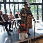 Zdjęcie zostało zrobione w Sali Wiejskiej w Urbanowie. Na scenie znajdują się cztery osoby. Jedna z nich stoi - to kobieta ubrana w granatową bluzkę w kropki i spódnicę w kolorowy wzór. Na głowie ma cylinder. Za nią siedzą przy stole trzy osoby. Od lewej pan ubrany w garnitur, trzymający akordeon, kobieta ubrana w biała sukienkę w czerwone kwiaty i pan ubrany w garnitur z muszką. Za nimi są wielkie okna, przez które wpada światło.