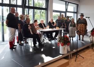 Zdjęcie zostało zrobione w Sali Wiejskiej w Urbanowie. Na scenie znajduje się 11 osób. Są różnokolorowo ubrani. Cztery z ich siedzą przy stole. Za nimi są wielkie okna, przez które wpada światło.
