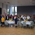 Zdjęcie zostało zrobione w Sali Wiejskiej w Urbanowie. Zdjęcie przedstawia zgromadzoną publiczność, która stoi przy okrągłych stolikach.