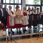 Zdjęcie zostało zrobione w Sali Wiejskiej w Urbanowie. Na scenie stoi 11 osób. Trzy kobiety pochodzą z zespołu Rudniczoki i mają czerwone suknie z białymi fartuszkami. Reszta osób ubrana jest w ciemne ubrania.Za nimi są wielkie okna, przez które wpada światło.
