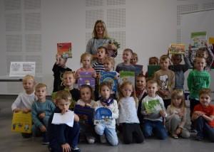 Zdjęcie zostało zrobione w sali widowiskowej nad OSP. Jest to zdjęcie grupowe. Przed panią trzymającą kwiatki stoją i kucają dzieci, które trzymają książki.