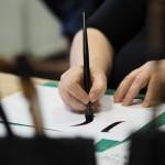 Zdjęcie przedstawia motyw pisania szeroką stalówką. Na zdjęciu widzimy kartkę, rękę kobiety w średnim wieku i fragment narysowanej litery.