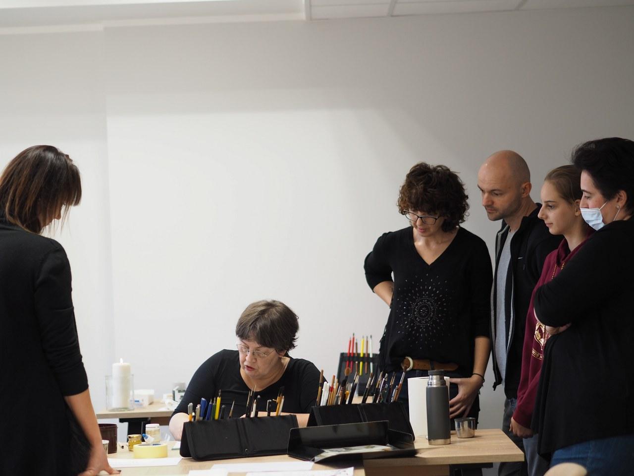 Na zdjęciu widzimy na środku siedzącą kobietę, pokazującą jak używać stalówki. A wokół niej stoją kobiety i mężczyźni.