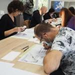 Na zdjęciu widać uczestników warsztatów, którzy w skupieniu ćwiczą podstawy kaligrafii.