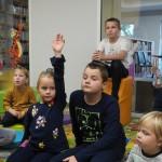 Zdjęcie zostało zrobione w bibliotece CKiB w Opalenicy. Widać na nim dzieci. Dziewczynka ubrana na granatowo na pierwszym planie ma podniesioną rękę.
