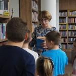 Zdjęcie zostało zrobione w Bibliotece w CKiB. Dzieci na pierwszym planie stoją odwrócone tyłem do aparatu i oglądają regały. Kobieta w średnim wieku tłumaczy im. W ręce trzyma książki. Jest odwrócona przodem do kamery.