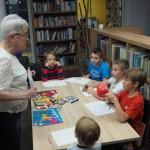 Zdjęcie zostało zrobione w bibliotece CKiB w Opalenicy. Na zdjęciu wśród regałów podstawiony jest stół, na którym leżą kolorowe kredki i białe kartki papieru. Wokół stołu siedzi pięciu chłopców. Przed nimi stoi starsza kobieta tłumacząca zasady zabawy.