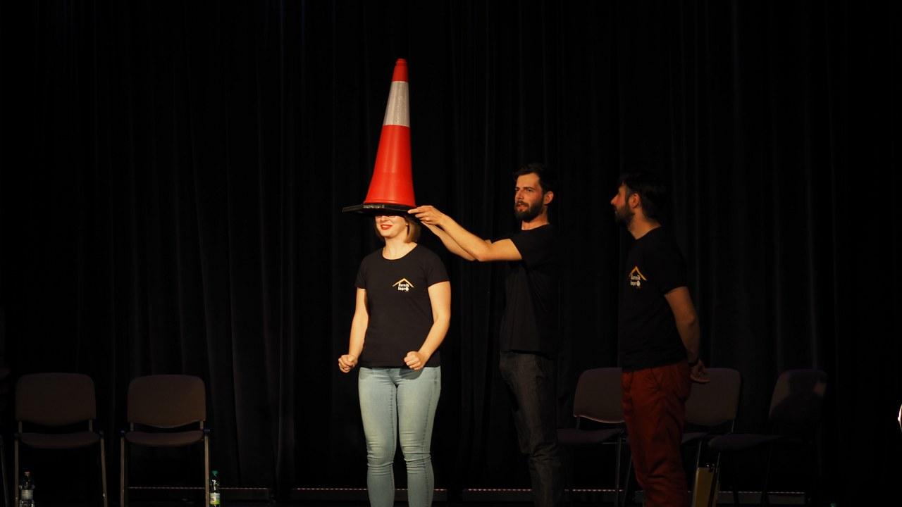 Zdjęcie zostało zrobione w sali widowiskowej CKiB w Opalenicy. Na scenie widzimy trzech aktorów, jedną kobietę i dwóch mężczyzn. Kobieta ma założony na głowie słupek drogowy.
