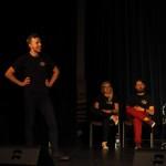 Zdjęcie zostało wykonane w sali widowiskowej CKiB w Opalenicy. na scenie na pierwszym planie stoi młody mężczyzna trzymający się za boki. Za nim na krzesłach siedzą po lewej stronie kobieta - blondynka, po prawej mężczyzna