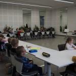 Zdjęcie zostało zrobione w sali widowiskowej nad OSP. Na zdjęciu widać dzieci siedzące przy długich, białych stołach.