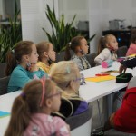 Zdjęcie zostało zrobione w sali widowiskowej nad OSP. Wokół stołu siedzą dzieci.