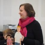 Zdjęcie zostało zrobione w sali widowiskowej nad OSP. Widzimy na nim kobietę w średnim wieku - autorkę. Trzyma w ręce lalki przedstawiające bohaterów jej książek.