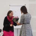 Zdjęcie zostało zrobione w sali widowiskowej nad OSP. Na zdjęciu są dwie kobiety - kobieta w szarej sukience, odwrócona tyłem do aparatu podaje kwiaty uśmiechniętej kobiecie w różowej spódnicy i czarnym swetrze.