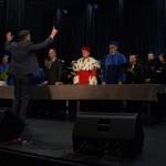 Zdjęcie zostało zrobione w sali widowiskowej CKiB. Na pierwszym planie widać odwróconego plecami do kamery dyrygenta, ubranego w ciemny garnitur z podniesionymi rękoma. Przed nim, przodem do aparatu stoją rektor, dziekani i burmistrz, a za nimi chór.