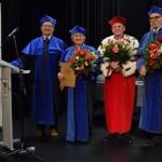 Zdjęcie zostało zrobione w sali widowiskowej CKiB w Opalenicy. Na pierwszym planie widać trójkę dziekanów ubranych na granatowo i rektora UTW ubranego na czerwono. Trzy osoby - kobieta i dwóch mężczyzn obok niej trzymają kwiaty.