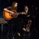 Zdjęcie zostało zrobione w sali widowiskowej CKiB w Opalenicy. Przedstawia dwie dziewczyny, jedna z nich po lewej stronie trzyma gitarę, druga po prawej śpiewa.